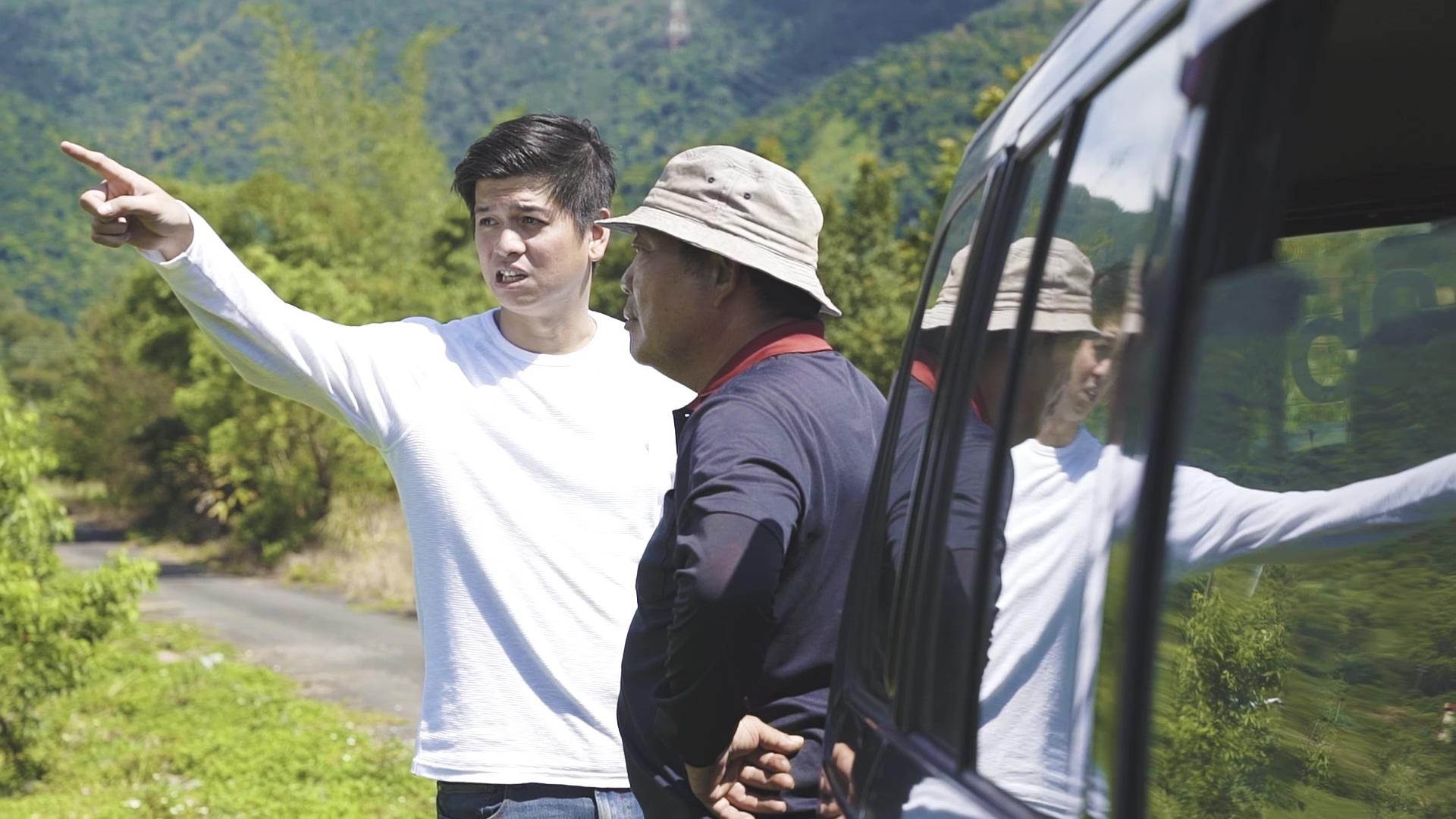 ▲趙文豪(左)與農民蘇連萬(右)於契作農場前討論苦茶樹事宜。