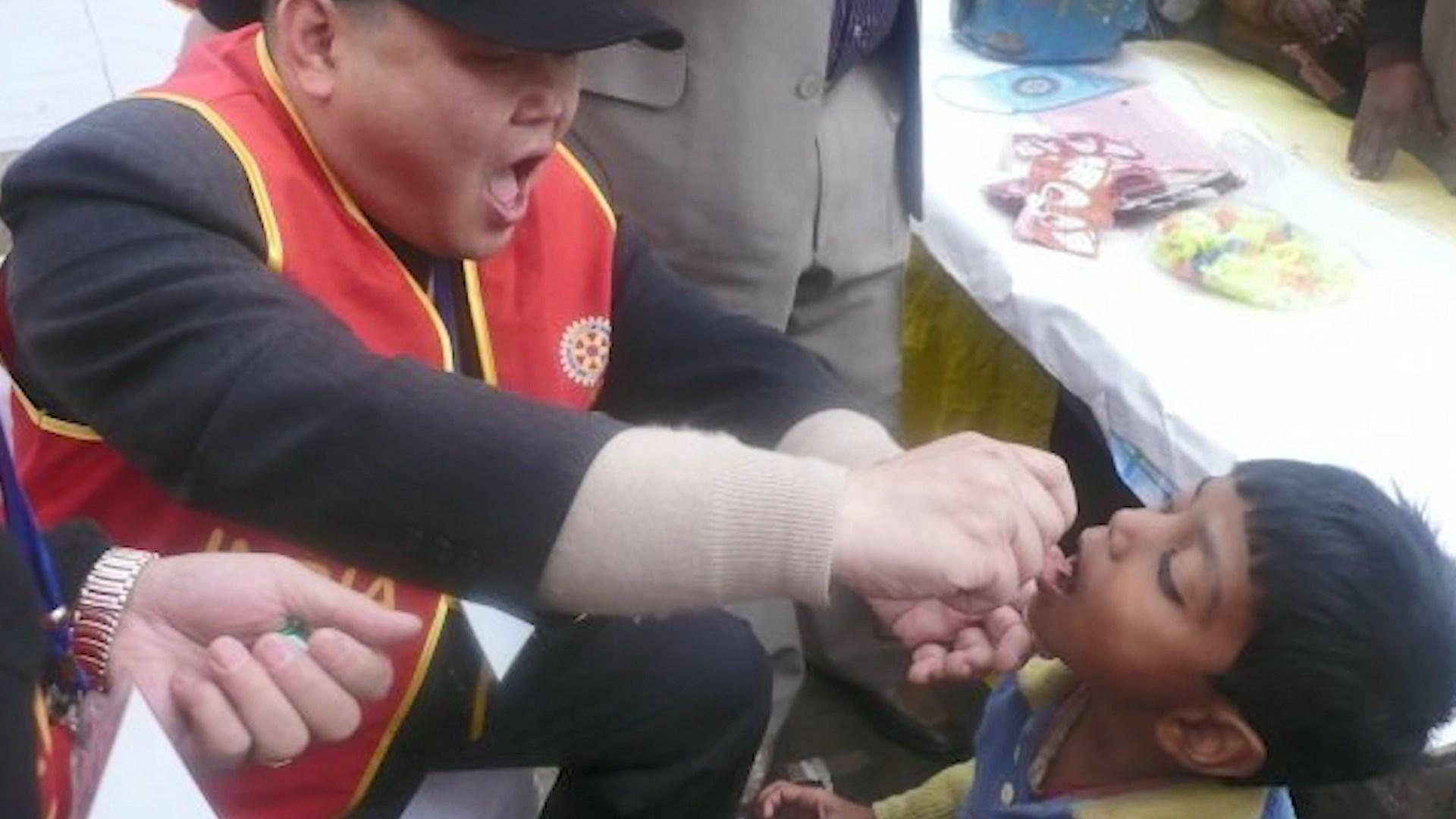 2010年,國際扶輪3482地區總監周佳弘與妻子到印度新德里協助當地幼兒接種小兒麻痺疫苗。