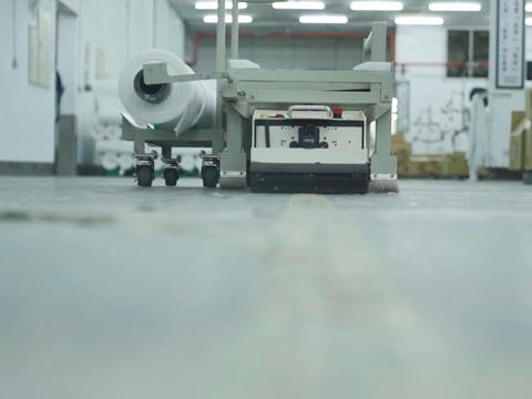 AGV無人搬運車可透過雲端智慧技術,自動到達完成織布工作的機台,搬運布料。