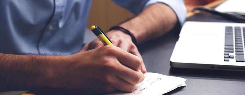 机上でノートをとる人