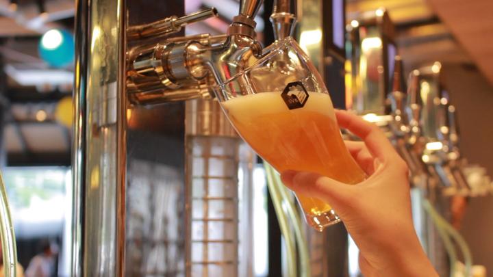サーバーからグラスにクラフトビールを注ぐ様子