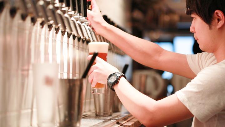 ビールをグラスに注ぐ男性