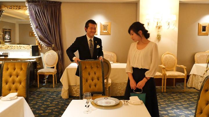 サービスマンが椅子を引いた椅子に座ろうとしている女性