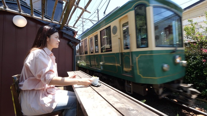 カフェから江ノ電を見る女性