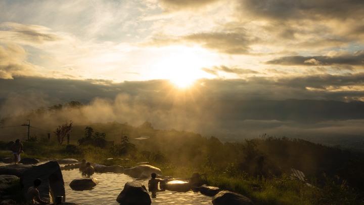 日が昇る景色を眺めながら温泉に入る人たち