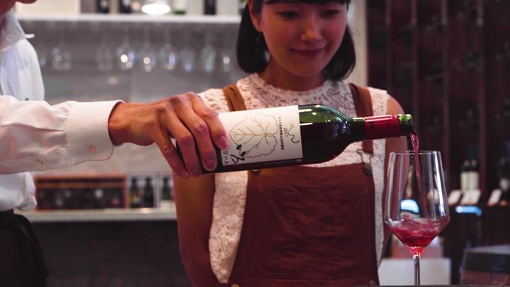 ワインをグラスに注ぐ様子を見る女性