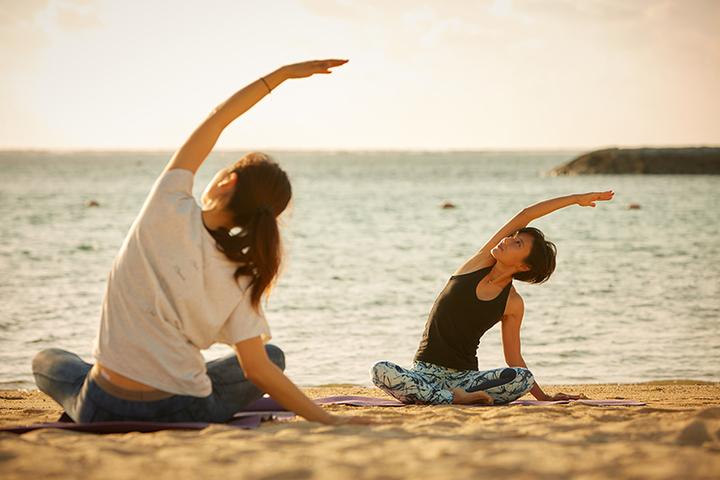 海の浜辺でヨガをする女性2人