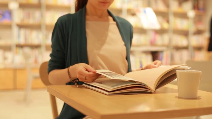 コーヒーを飲みながら本を読んでいる女性