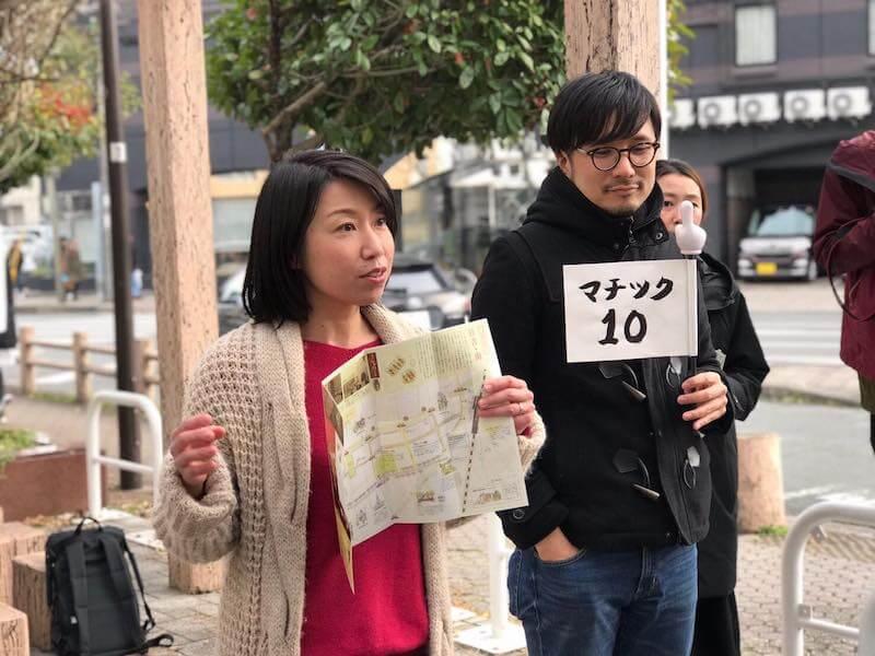 まち歩きの説明をする久留米市役所の眞武さん。まち歩き、プレゼン、懇親会と1日がかりのツアー開始。