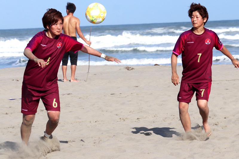 鴨川の砂浜でビーチサッカーの練習に勤しむ石井さん(左)と田中さん(右)