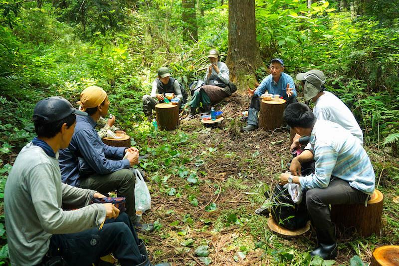 協力隊員の村上さんと斎藤さんが前日に用意した丸太のベンチで昼食休憩