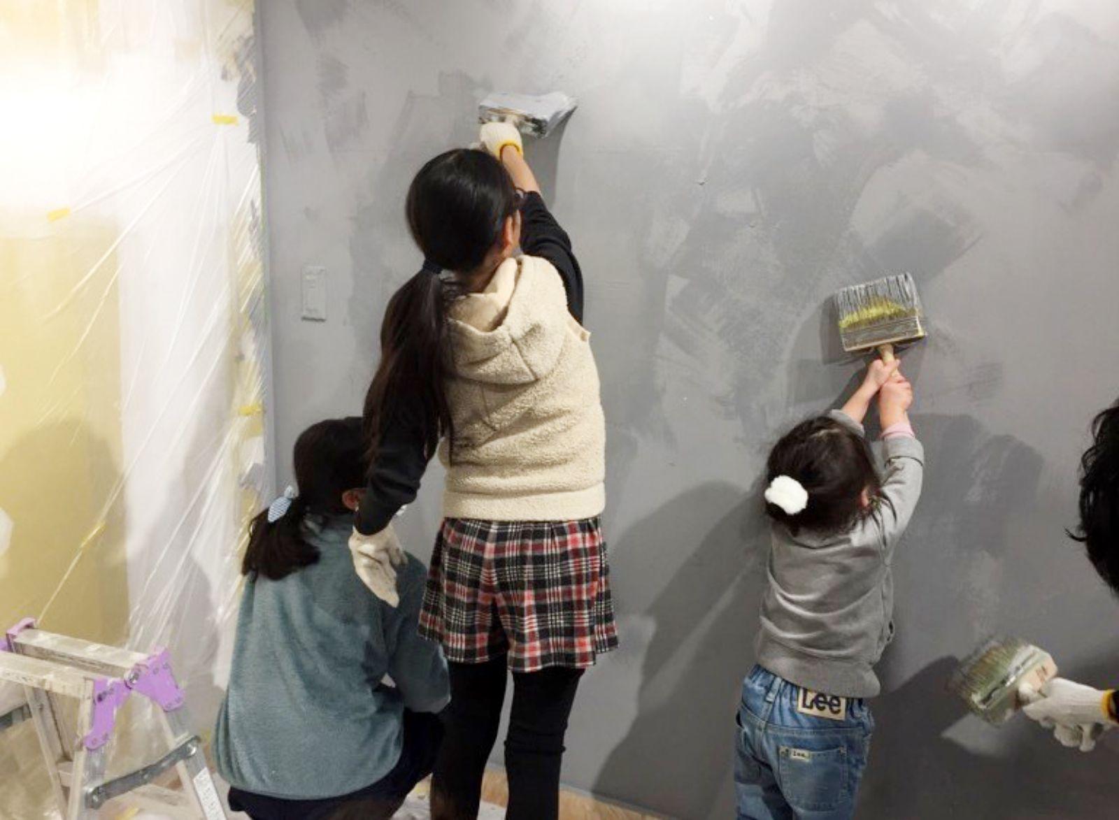 オープン前の店舗の壁を一生懸命に塗る地域の子どもたち