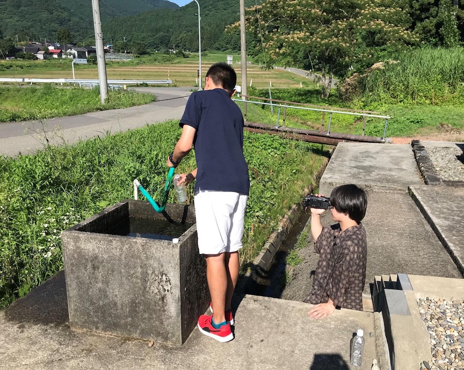 地域のPRのため、湧き水のCM撮影をするメンバー