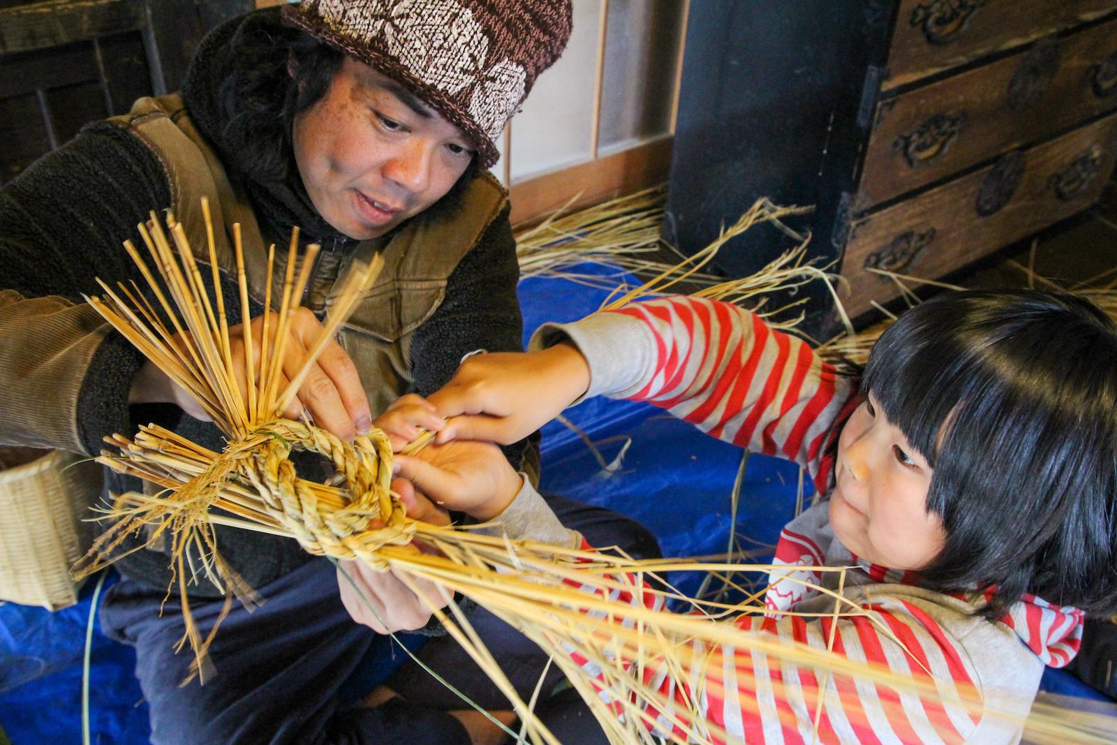 親の輪飾りに足になる子の稲藁を挿し込む。藁細工は里山の大切な手仕事
