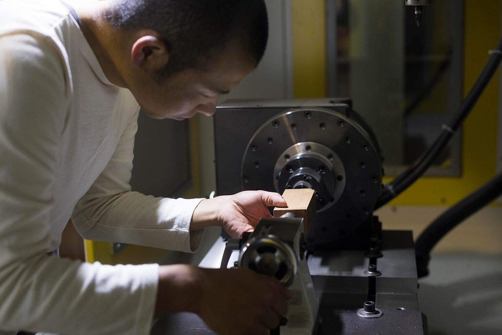 製品の切削のために、CNC機器に端材をセットする小石さん