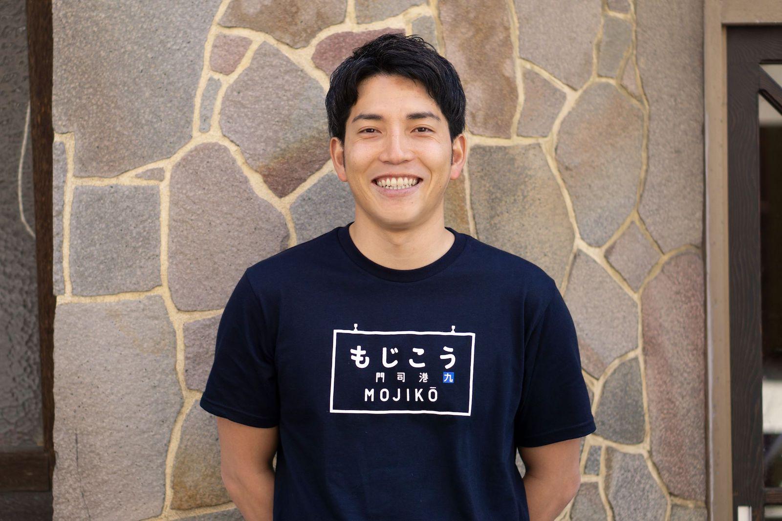 代表の菊池勇太 ゲストハウス「ポルト」の前で撮影