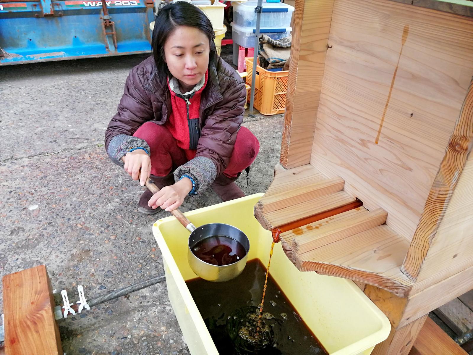 【醤油作り】自家製のお米と大豆で醤油を仕込み、熟したもろみに圧をかけて絞ります。