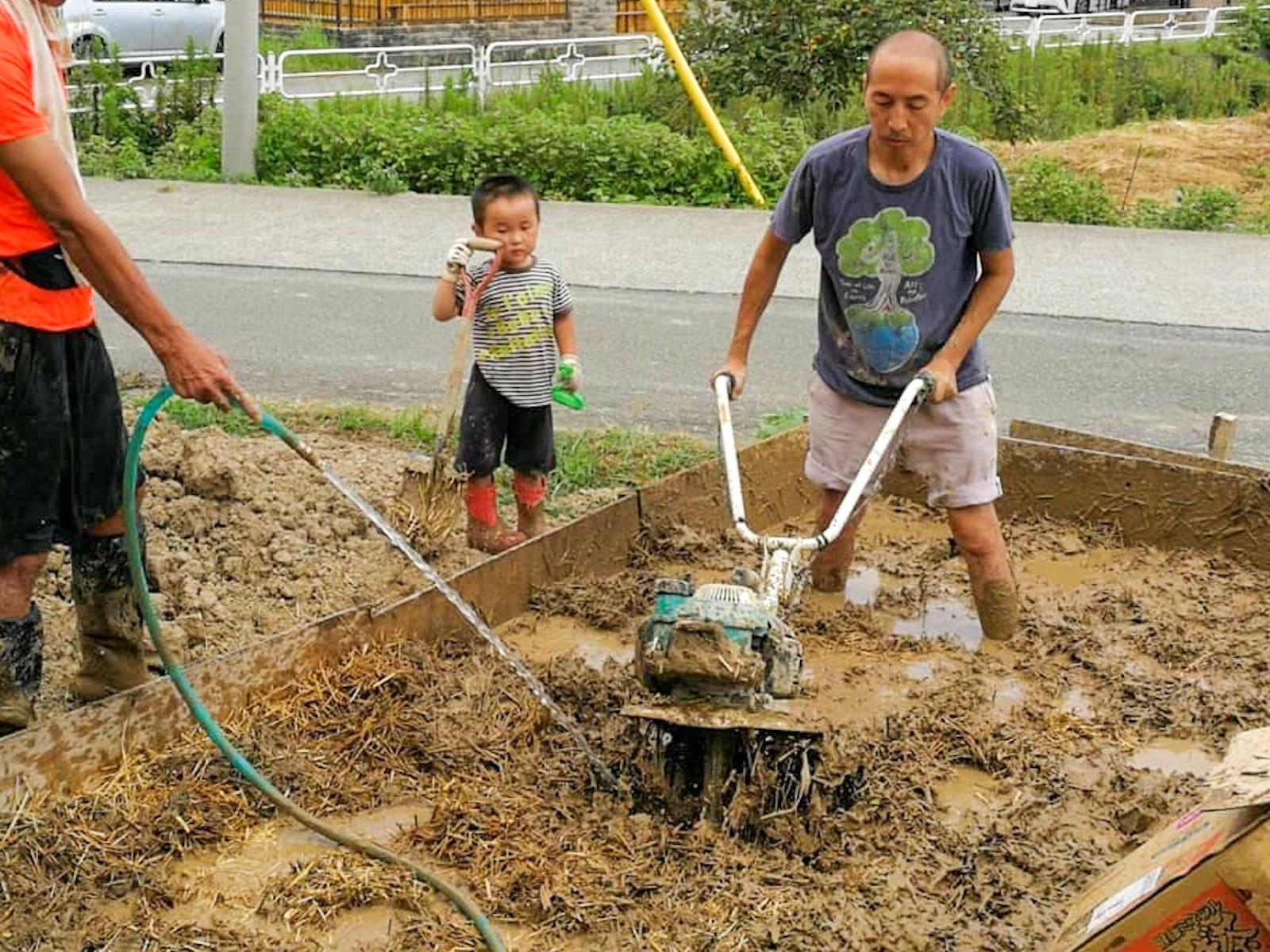 """耕運機で土と稲わらを混ぜる山口さん。""""大きな池で泥遊びしてる感じ""""。"""