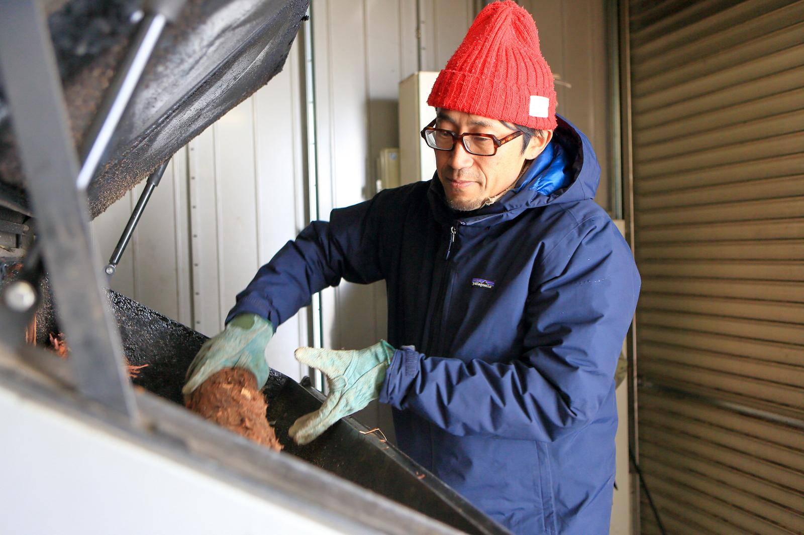 温泉施設に導入している薪ボイラーに薪を投入する井筒さん 写真提供:sonraku