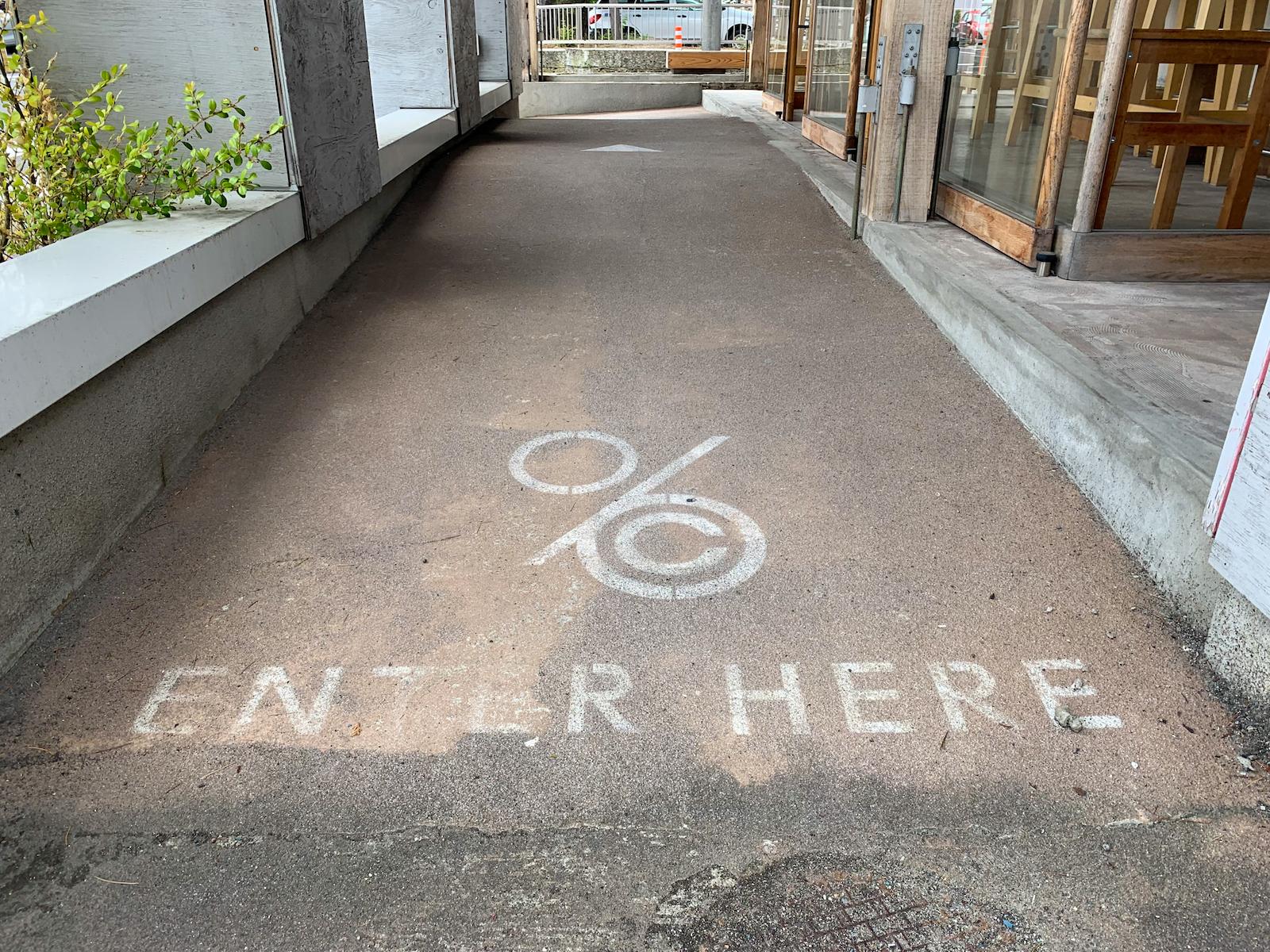 店舗前の路面に、ロゴマークとENTER HEREと書かれている