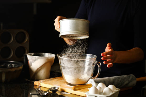 Woman sifting flour through...