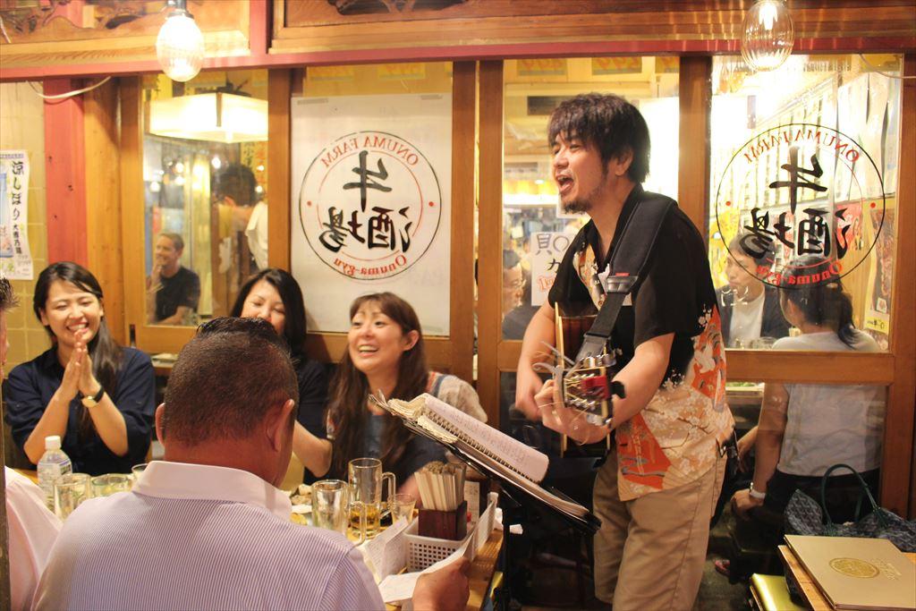 客を前に歌う流しのシンガーソングライターの男性