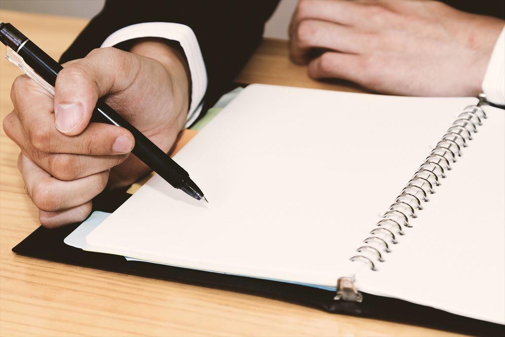 ノートに文字を書こうとする男性