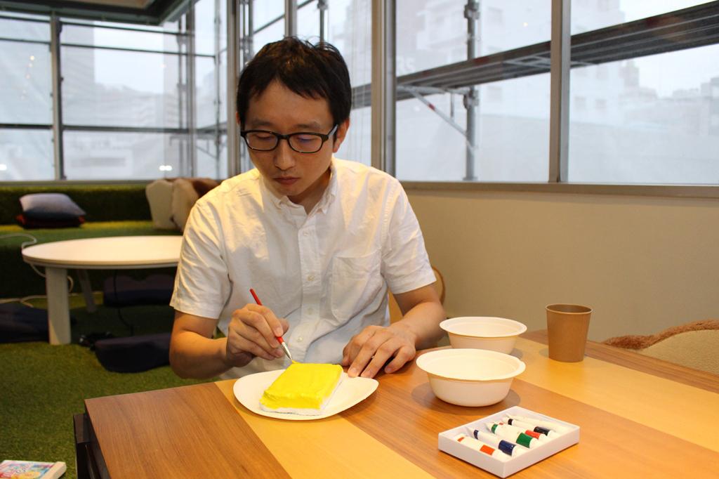 紙粘土を着色する斎藤さん