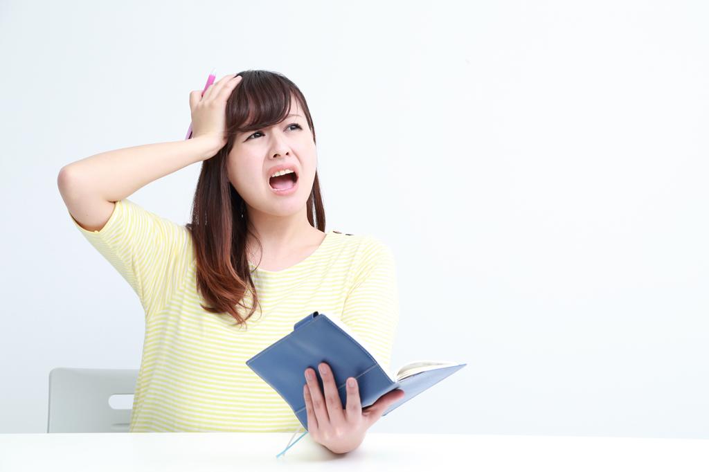 手帳を見て慌てる女性