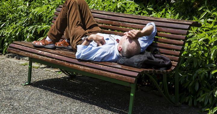 熱中症でベンチに横になるサラリーマンの男性