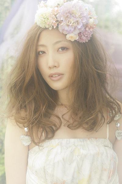ゆるふわの髪に花を乗せこちらを見つめる歌手活動中のティアラ