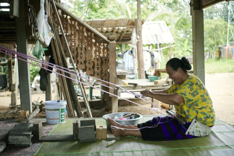 タイに暮らすラフ族の作り手。『身の腰と家の柱などに縦糸をはり、簡単な織り機具で布を織る「腰織り」と呼ばれる作業をしている