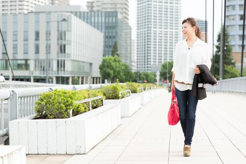 街を背景に歩くビジネスウーマン