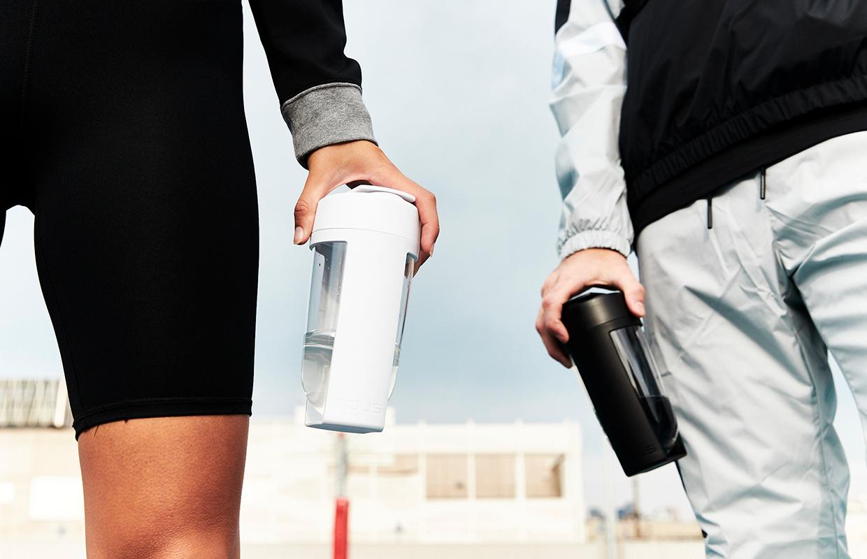 一名女子拿著MOUS Fitness 運動健身搖搖杯,莫蘭白色,另一名男子拿著MOUS Fitness 運動健身搖搖杯,黑色