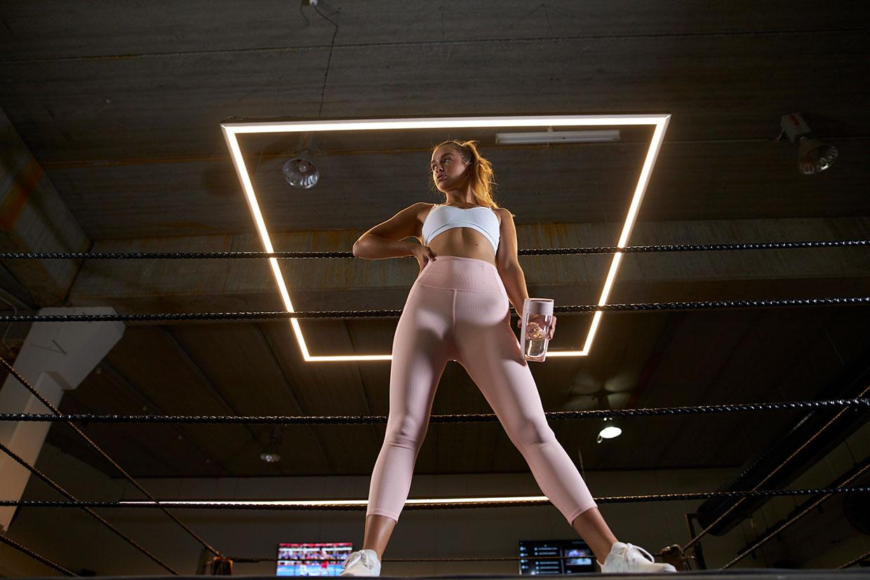 一名女子拿著MOUS Fitness 運動健身搖搖杯,腮紅粉色站在擂台旁
