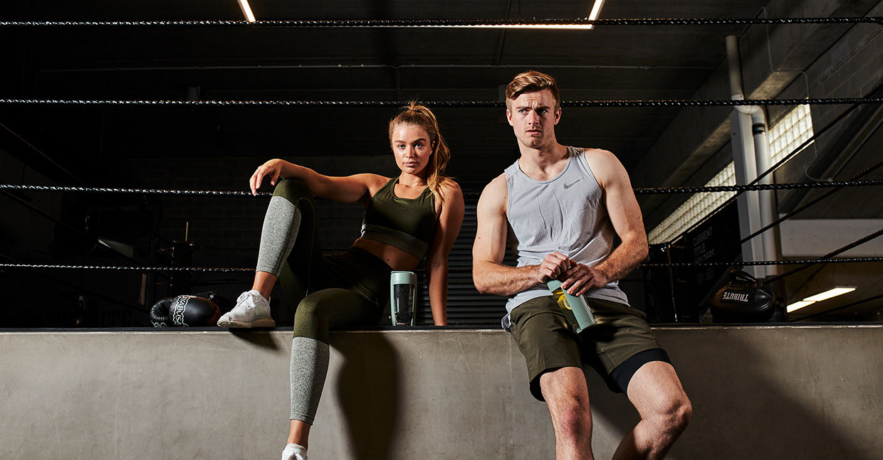 女子及男子拿著MOUS Fitness 運動健身搖搖杯,莫蘭迪綠色站在擂台旁