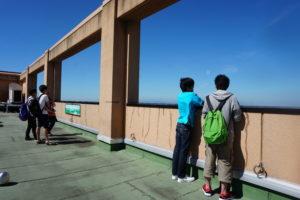 オープンキャンパスが終了する15時半ギリギリまで、学生スタッフが同行する学内キャンパスツアーも行っておりました。今皆さんがいるのは本学で1番背の高い建物、中央館の屋上です。屋上には本学に入学してしまうと入れなくなるので、オープンキャンパスに参加してくれた方だけの特権です!ちなみにどんな景色なのかと言うと…