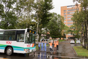 朝は晴天でしたが、お昼を過ぎたあたりから雨が降ってきてしまい、皆さんが帰る頃にはすっかり雨模様でした。しかしそんな雨にも負けない学生スタッフは無料送迎バスで帰る皆さんをお見送り。