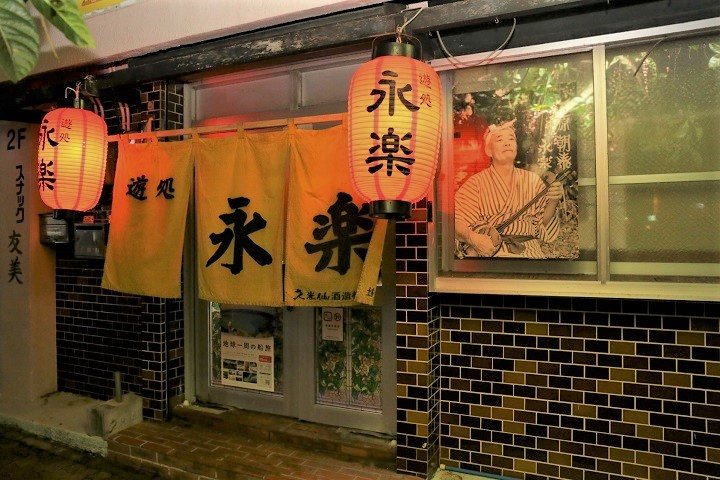 """Music belongs to everyone."" With heartwarming hospitality and delightful regular customers, the folk music Izakaya [Ashibidukuru Eiraku] in Sakaemachi, Naha City, welcomes all."