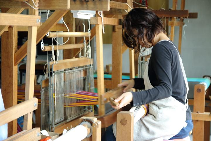 機織り機で作品を制作中の作家さん