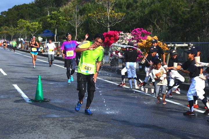 古宇利島ハーフマラソンのランナーが水をかけられている写真