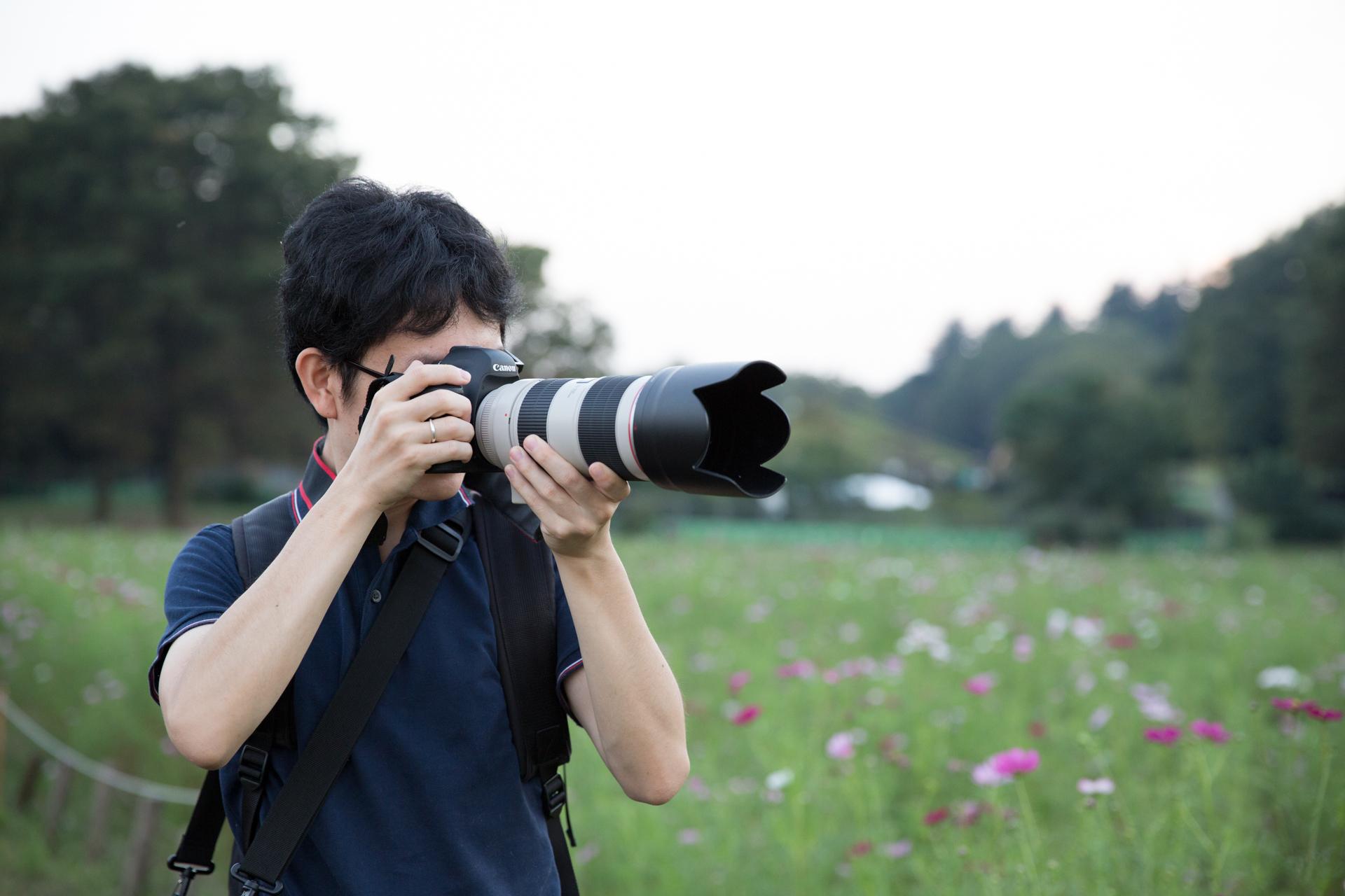 一眼レフカメラと望遠ズームレンズを持った男性