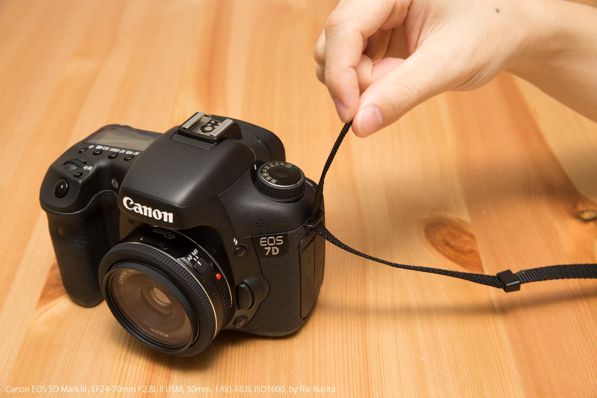 カメラのストラップ取り付け部にネックストラップを下から通しているところ