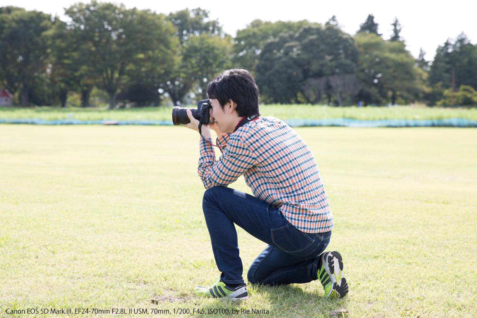 しゃがんだ状態で左膝を立て、その上に左肘を置くカメラの構え方