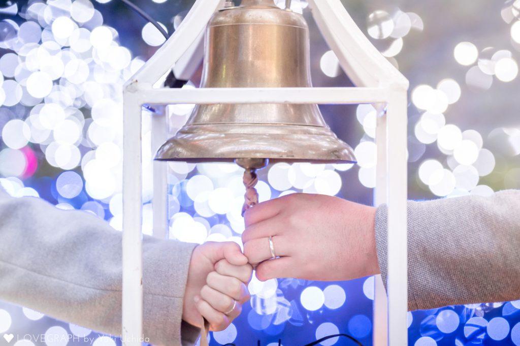 鐘を鳴らす男女の手