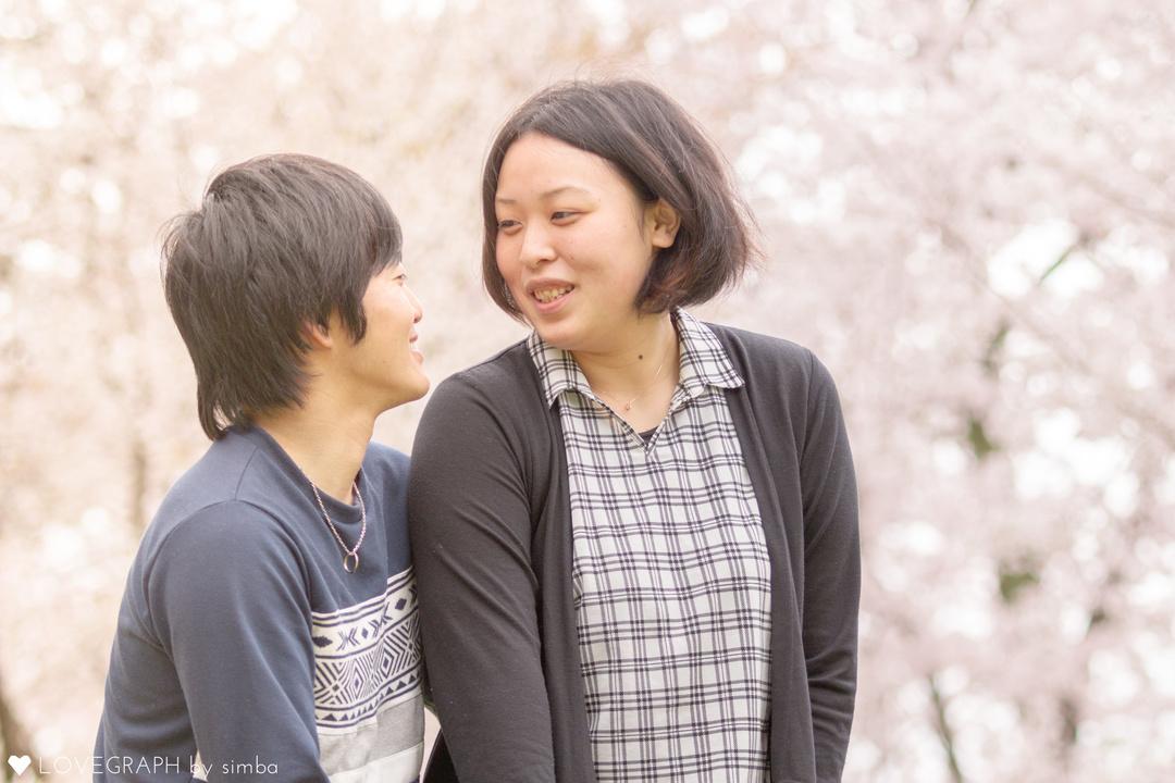 桜の下で並んで立つカップル