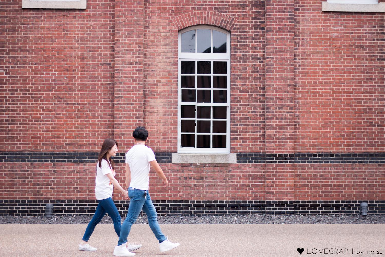 レンガの建物の前を並んで歩くカップル