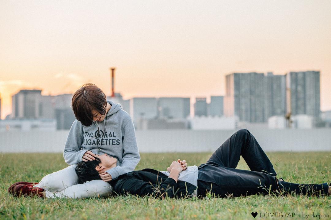 夕日を背景に膝枕をする女性と、寝転ぶ男性