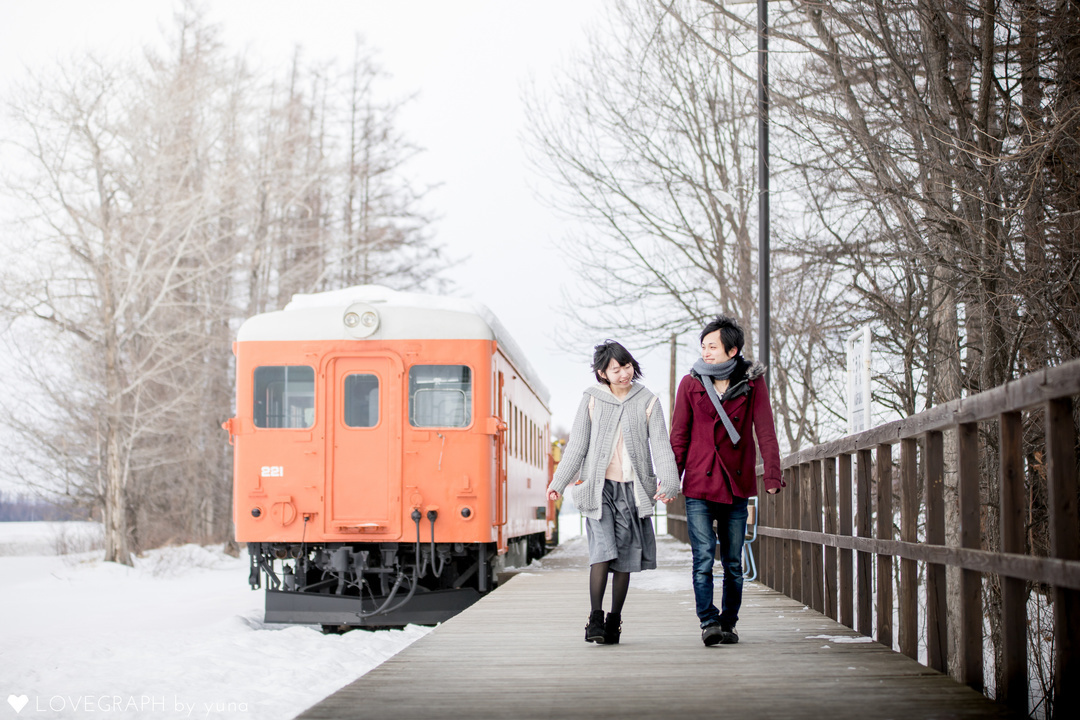 電車のホームを並んである男女
