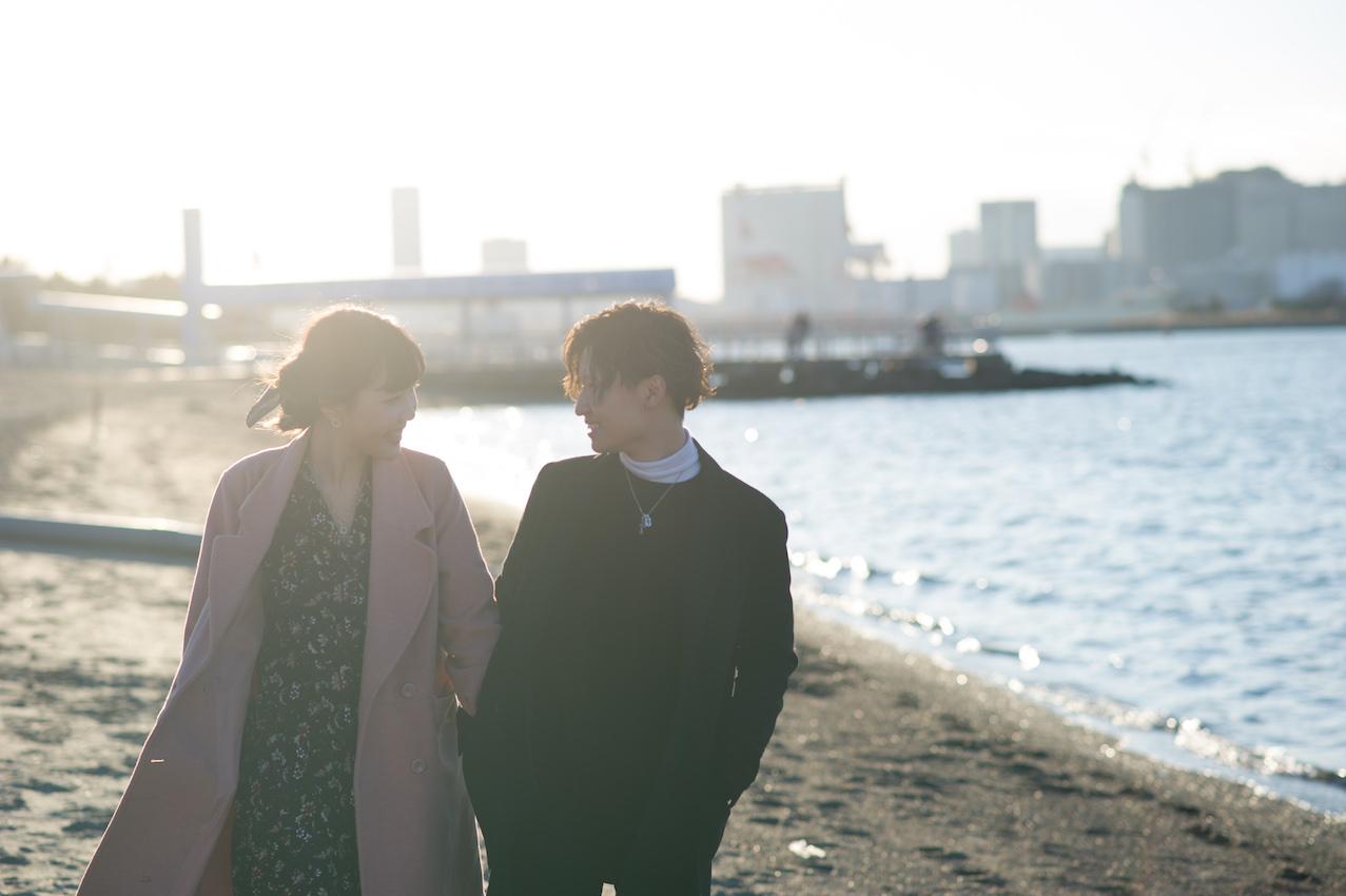 浜辺で手をつないで歩くカップル